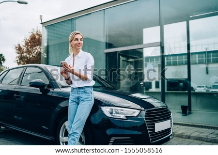Cheerful lady with cheerful smile dressed in casual clothes standing on street and leaning on black car while chatting on smartphone with friends and looking away #1555058516