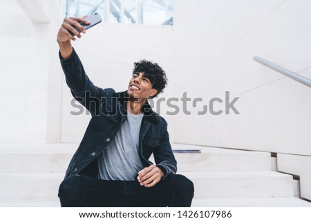 Cheerful Latino man with cellular gadget clicking selfie pictures on smartphone camera resting at city area, happy young male shooting video for blog in social networks using modern mobile phone #1426107986