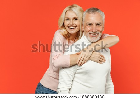 Cheerful laughing funny couple two friends elderly gray-haired man blonde woman in white pink casual clothes standing hugging looking camera isolated on bright orange color background studio portrait