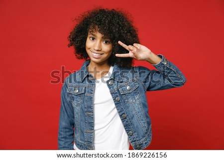 Cheerful little african american kid girl 12-13 years old in casual denim jacket showing victory sign isolated on bright red color background children studio portrait. Childhood lifestyle concept Stockfoto ©