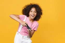 Cheerful little african american kid girl 12-13 years old in pink t-shirt isolated on yellow wall background studio portrait. Childhood lifestyle concept. Mock up copy space. Play game with joystick