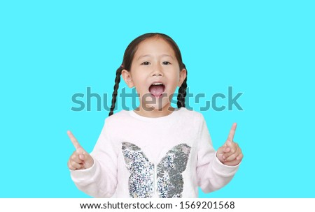 Cheerful little Asian child girl raised two forefinger to cheer isolated over cyan background. Cheerful emotion concept. #1569201568