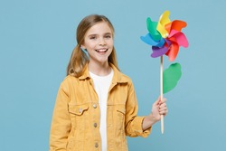 Cheerful little blonde kid girl 12-13 years old in yellow jacket posing isolated on pastel blue background studio portrait. Childhood lifestyle concept. Mock up copy space. Hold colorful toy windmill