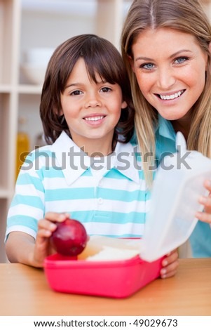 Cheerful little boy and his mother preparing his snack in the kitchen