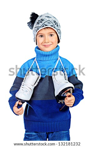 Cheerful little boy in warm sweater and hat  holding figure skates. Isolated over white background