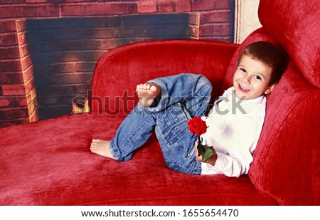 Cheerful little boy looking at camera posing on red sofa with red rose in hand over Christmas background with decorations. Cheerful childhood, happy holiday and baby little star concept.