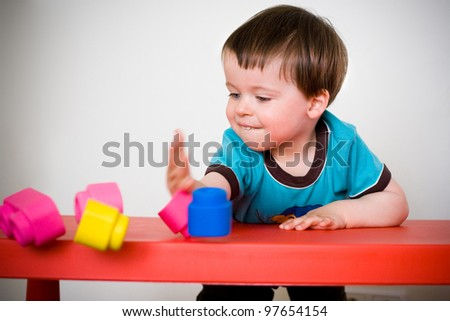 Cheerful little boy playing with colorful blocks