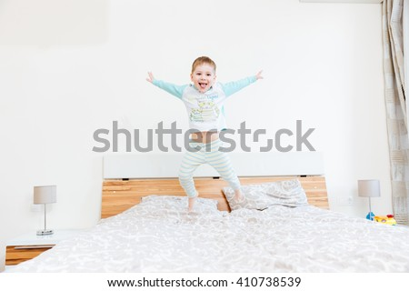 Cheerful little boy showing tongue and jumping on bed at home