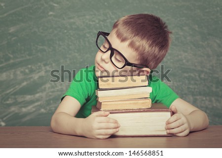 Cheerful  little boy sitting at the table. Looking at camera School concept