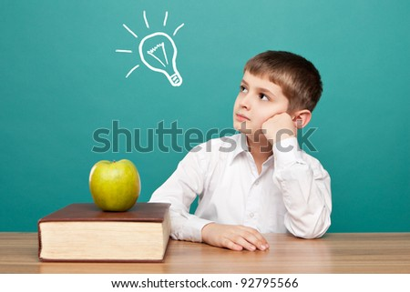 cheerful  little boy sitting at the table. School concept