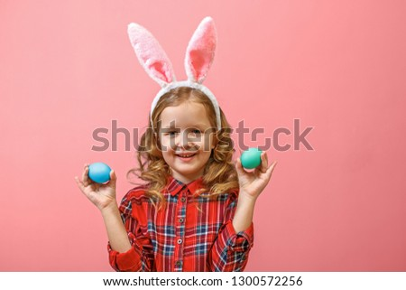 Cheerful little child girl with bunny ears with two Easter eggs on a colored background. #1300572256