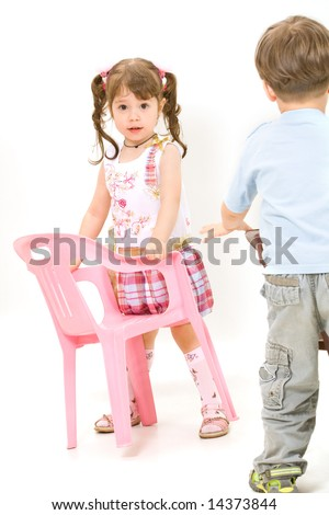 Cheerful little children with pink chair isolated over white