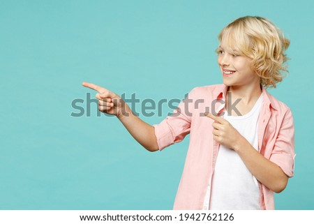 Cheerful little curly kid boy 10s years old wearing basic pink shirt pointing index fingers aside isolated on blue turquoise color background children studio portrait. Childhood lifestyle concept Stockfoto ©