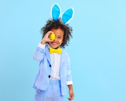 Cheerful little ethnic boy with Afro hair in Easter costume and bunny ears smiling while covering eye with colorful egg against blue background