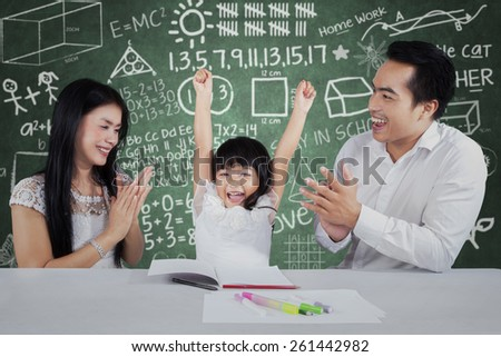 Cheerful little girl get appreciation and applause from her parents after studying
