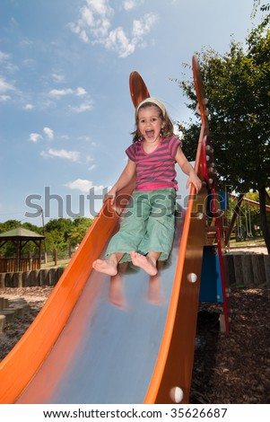 Cheerful little girl having fun while sliding down on the slide with bursting laugh