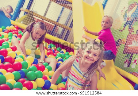 cheerful little girl in dress playing on playground with plastic balls with other kids