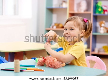 Cheerful little girl play in preschool, shallow DOF
