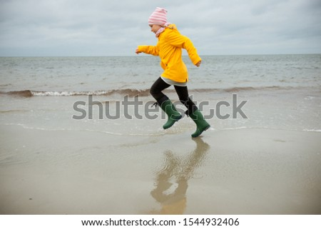 Cheerful little girl running on water of Baltic sea in rubber boots at cold and windy weather