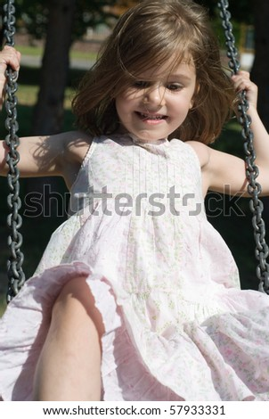 Cheerful little girl swinging on playground, looking away from the camera