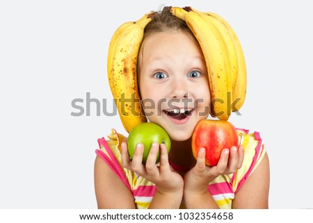 Stock Photo Cheerful little girl with apples, lemon and banana poses  in studio