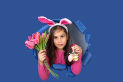 Cheerful little girl with bunny ears with an easter egg. Child in a round hole circle in colored yellow and blue backgrounds