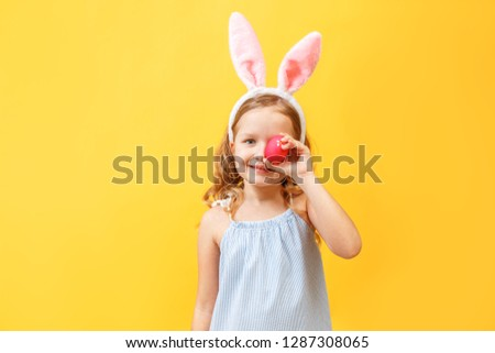 Cheerful little kid girl with bunny ears with an easter egg on a colored background. #1287308065