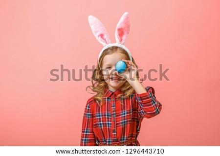 Cheerful little kid girl with bunny ears with an easter egg on a colored background. #1296443710