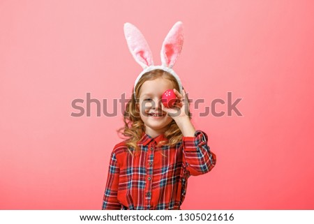 Cheerful little kid girl with bunny ears with an easter egg on a colored background. #1305021616