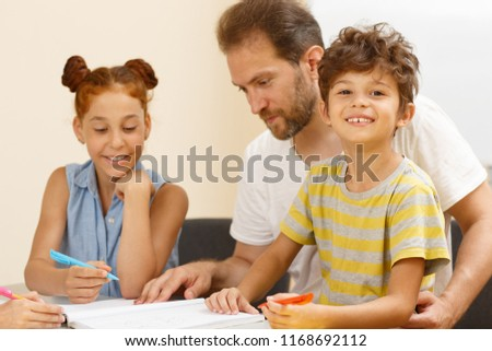 Cheerful little pupil of modern school sitting near male teacher, writing, looking at camera and posing in classroom. Cute schoolboy enjoying process of learning and interesting lesson. #1168692112