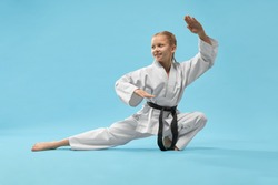 Cheerful little sports woman sitting on twine and practising karate on blue isolated background. Active girl wearing white kimono and black belt doing sport in studio. Concept of karate and jujitsu.