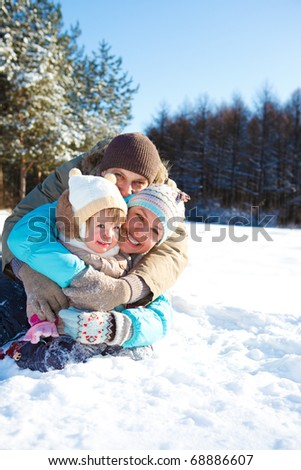 Cheerful loving family sit embracing in the winter park