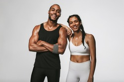 Cheerful male and female athlete standing together at gym. Smiling woman standing with her hand on shoulder of male friend.