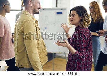Cheerful male and female colleagues having fun joking while resting after working session on break in coworking space, hipster girl communicating with friends telling interesting stories in good mood