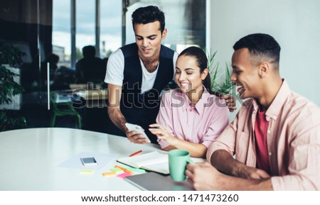 Cheerful male and female colleagues reading funny publication in social networks via app on cellphone during break from collaboration on startup, happy group of people smiling from joke on website