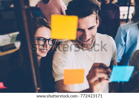 Cheerful male and female students planning working process using memo cards during brainstorming session, happy team members satisfied with having a lot of creative ideas writing on stickers