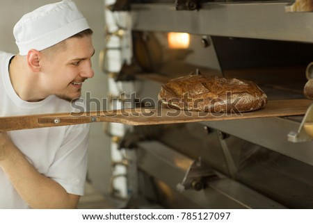 Cheerful male baker smiling while pulling out delicious fresh bread out of oven at his kitchen bakery food healthy natural professionalism manufacturing cooking occupation job working worker positive