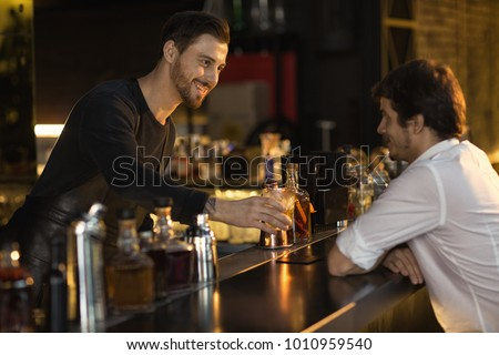 Cheerful male bearded bartender smiling giving his client a drink while working at the bar communication friendly positivity entertainment leisure occupation job luxury lifestyle club weekend service