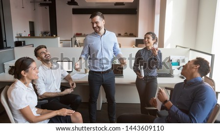 Cheerful male boss and diverse business team laughing at funny joke having fun at work break, happy leader mentor and multicultural workers interns enjoy teambuilding at group meeting in office room