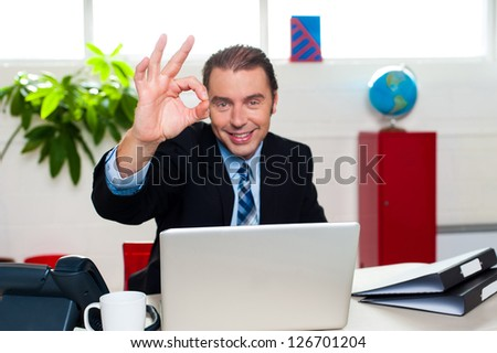 Cheerful male boss gesturing perfect sign while seated at his workstation.