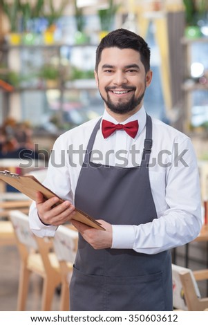 Cheerful male cafe worker is holding a menu. He is standing and smiling. The man is looking at camera happily