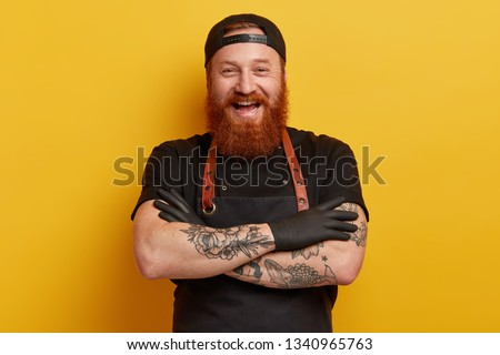 Cheerful male chef in black apron, t shirt and gloves, has thick long ginger beard, keeps arms folded, laughs sincerely, has break after cooking, talks with colleagues in restaurant, shares new recipe #1340965763