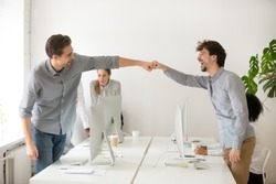 Cheerful male colleagues fist bumping celebrating successful teamwork in office, friendly happy motivated coworkers excited by good work result congratulating each other with professional achievement