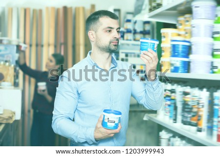 Cheerful male designer is holding paint for redecorate room in the store