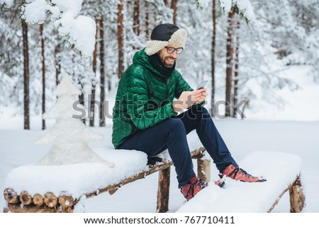 Cheerful male enjoys communication on smart phone and loneliness, calm atmosphere, sits on wooden bench covered with snow in winter forest, happy to recieve message from close friend