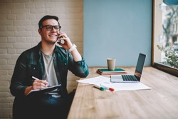 Cheerful male freelancer making telephone call share good news about project working in cafe interior,happy hipster guy having smartphone conversation while studying in good mood writing in planner