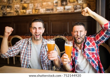 Cheerful male friends having fun at the beer pub celebrating victory of their favorite team watching game on TV