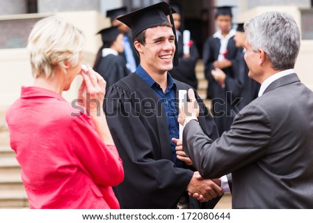 cheerful male graduate handshaking with his grandfather