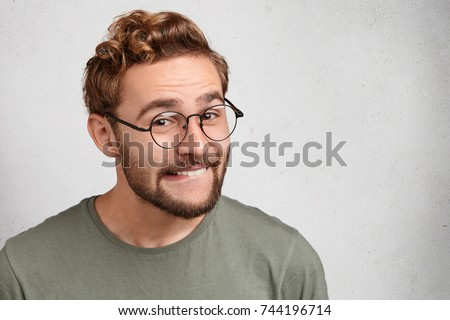 Cheerful male grins at camera, bits lower lip, being glad to achieve goals. Funny bearded young man with trendy hairdo, wears glasses, smiles pleasantly, expresses positive emotions and feelings - Shutterstock ID 744196714