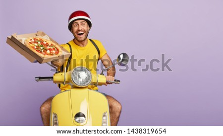 Cheerful male restaurant worker holds opened box of delicious tomato pizza, offers to taste, has broad friendly smile, rides motorbike, delivers food free, isolated on purple wall. Pizzeria delivery